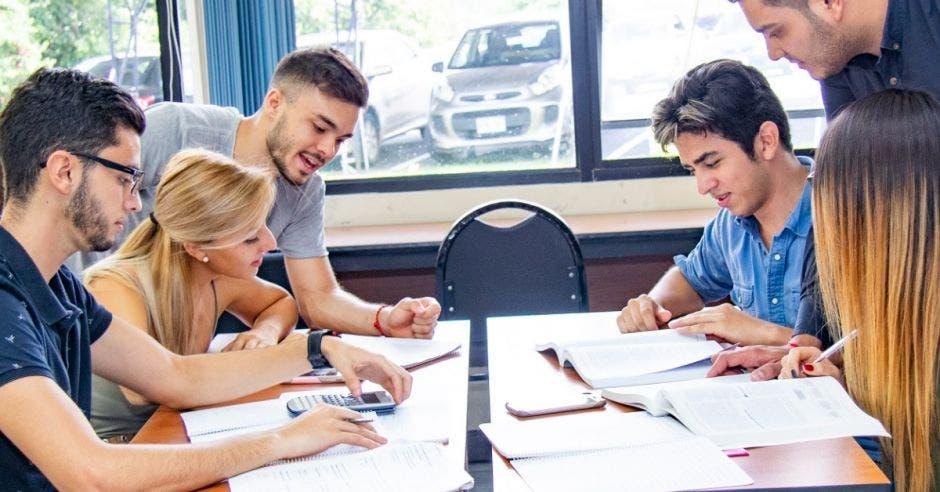 jóvenes en grupo estudiando en una mesa
