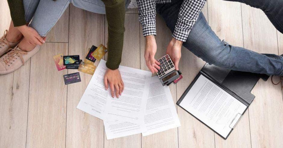 Mujer y hombre sacando cuentas en el piso con papeles