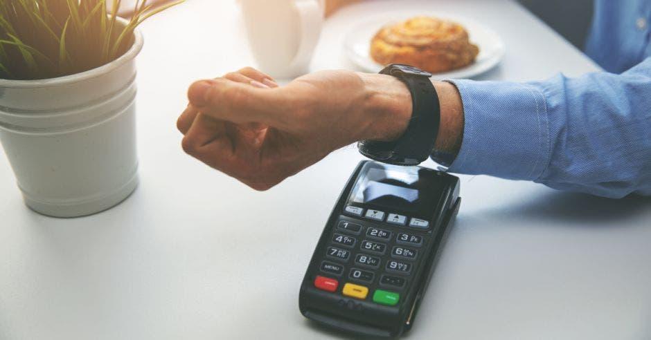 hombre pagando en un datáfono a través de su reloj inteligente