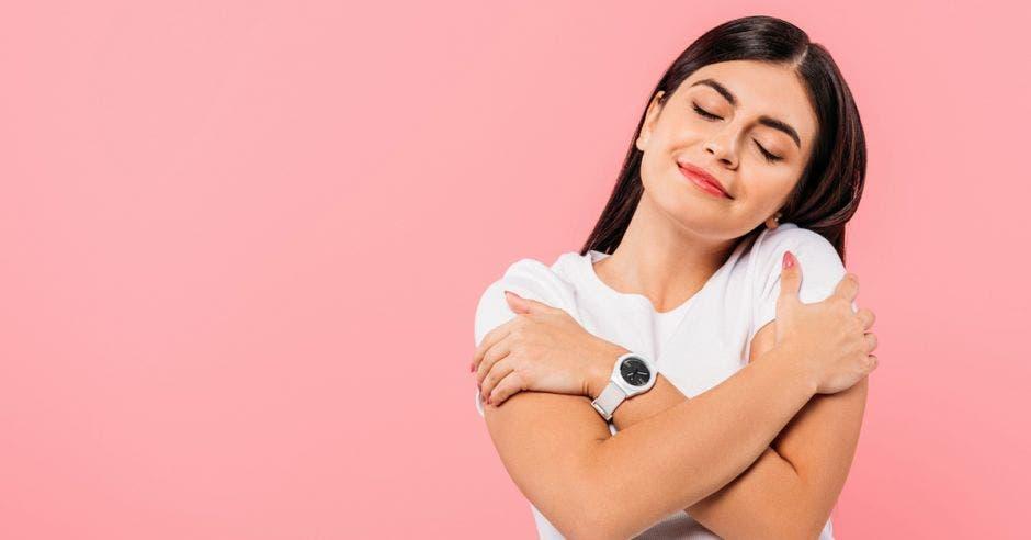 Mujer con blusa blanca con fondo rosa