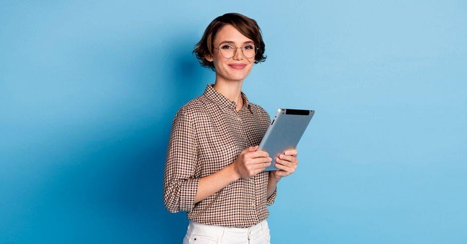 Mujer con una tablet en sus manos y con fondo de pared celeste