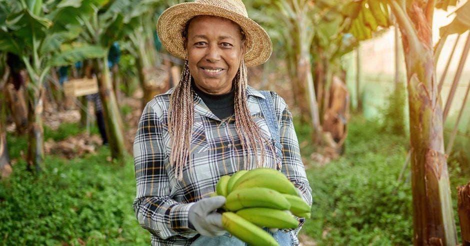 Una mujer sosteniendo ocho bananos