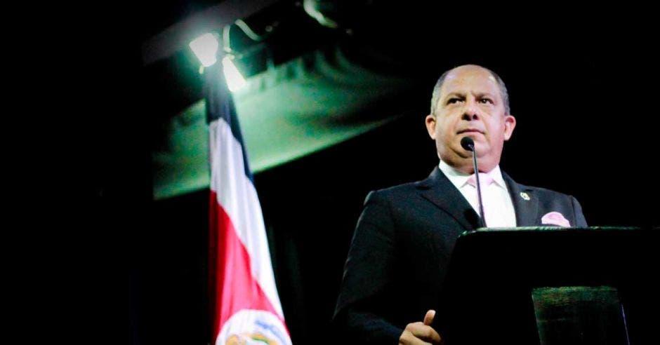Luis Guillermo Solís en una conferencia con la bandera de Costa Rica atrás